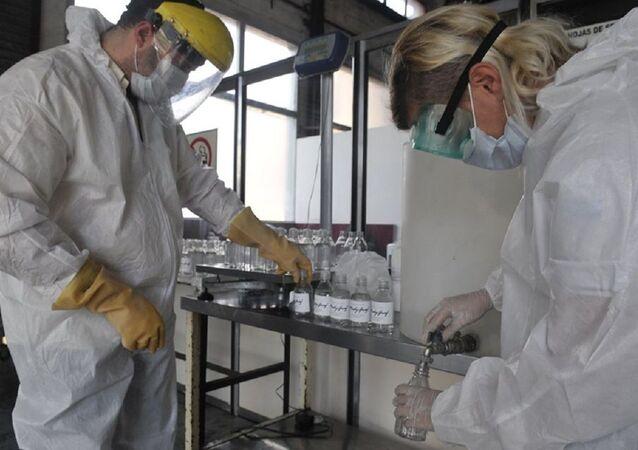 Trabajadores de Madygraf haciendo alcohol en gel