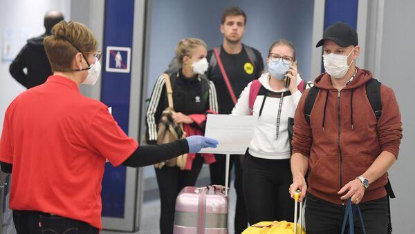 Unos turistas con mascarillas en un aeropuerto - Sputnik Mundo