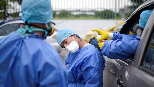 Médicos de un hospital de Guayaquil, Ecuador, se desinfectan durante sus jornadas - Sputnik Mundo
