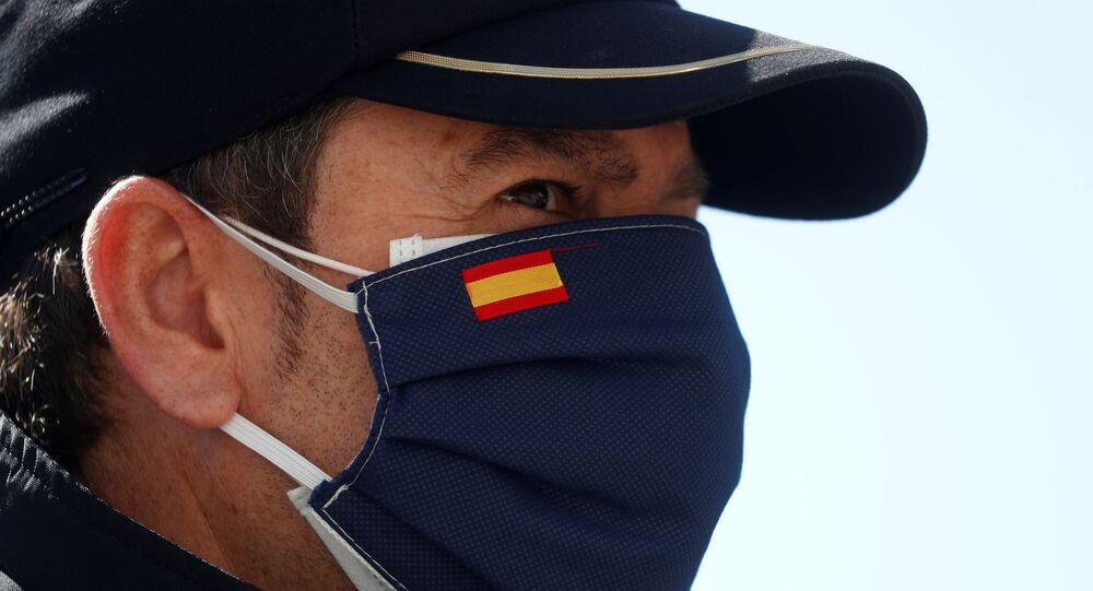 Una persona con una mascarilla que lleva la bandera esañola