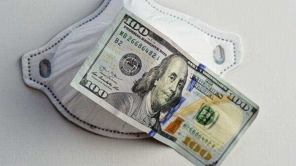 Una mascarilla junto a un billete de 100 dólares. Imagen referencial - Sputnik Mundo