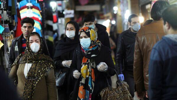 Personas usan mascarillas y guantes protectores mientras caminan en Teherán, Irán - Sputnik Mundo