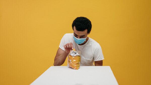 Unos en mascarilla comiendo patatas fritas - Sputnik Mundo