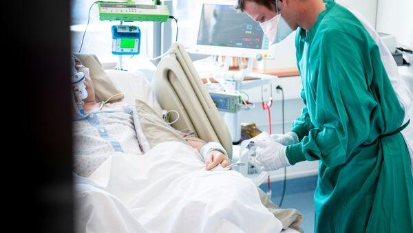 Un médico con un enfermo de COVID-19 - Sputnik Mundo