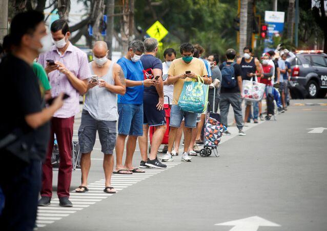 Hombres haciendo una fila al supermercado en Perú