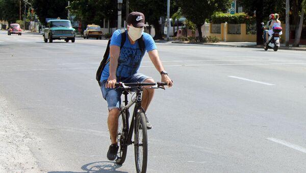 Un ciclista en mascarilla en Cuba - Sputnik Mundo