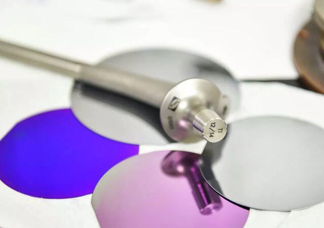 Un implante de titanio junto con muestras de recubrimientos antigérmenes