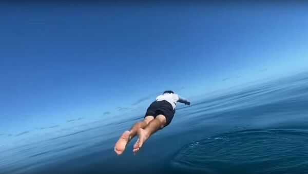 Un pescador se lanza al agua por su caña de pescar - Sputnik Mundo