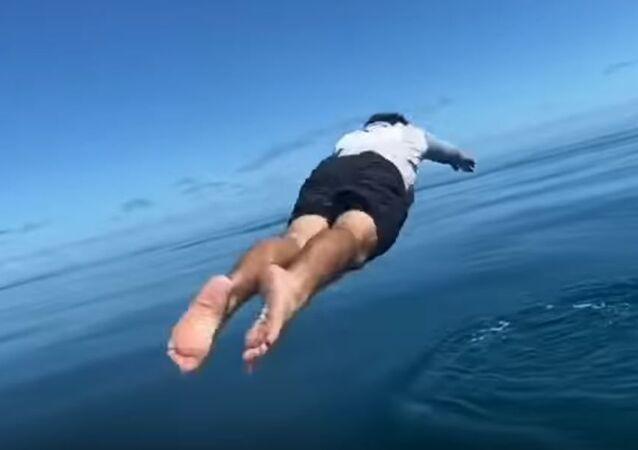 Un pescador se lanza al agua por su caña de pescar