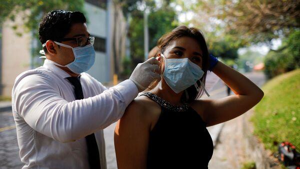 Un chico y una chica con mascarillas durante el brote del coronavirus en El Salvador - Sputnik Mundo