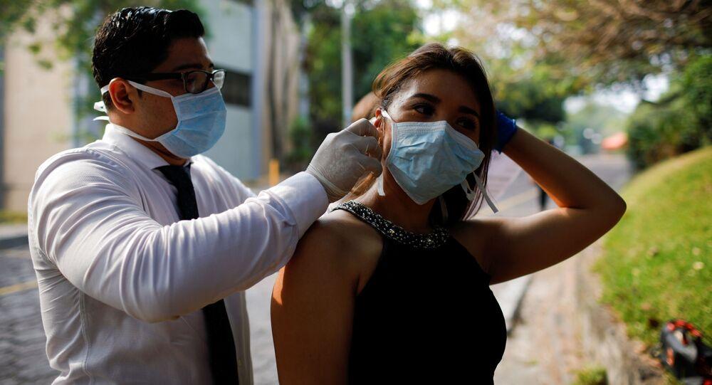 Un chico y una chica con mascarillas durante el brote del coronavirus en El Salvador