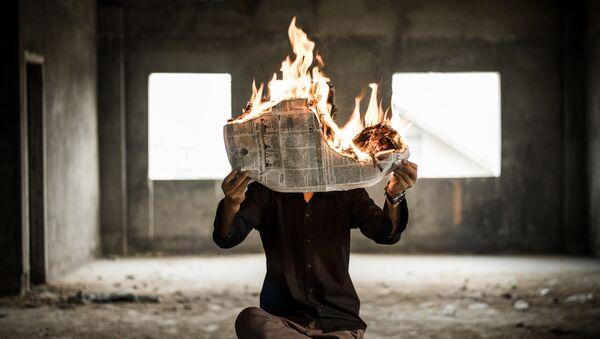 Un hombre con el periódico ardiente (imagen referencial) - Sputnik Mundo