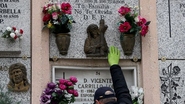 Un hombre cerca de la tumba de sus padres tras la muerte de su madre del coronavirus en España - Sputnik Mundo