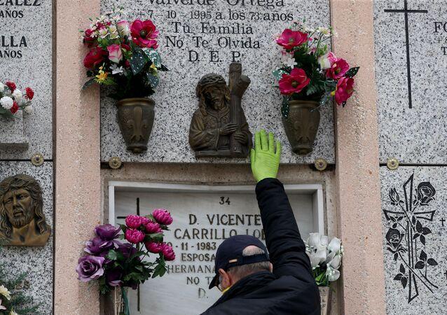 Un hombre cerca de la tumba de sus padres tras la muerte de su madre del coronavirus en España