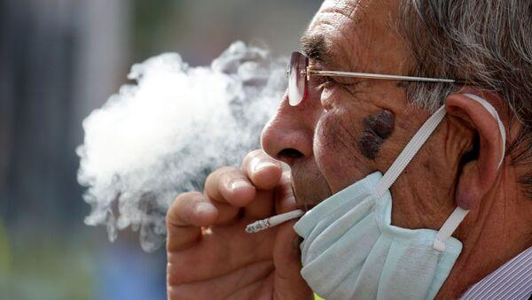 Hombre con mascarilla fumando - Sputnik Mundo