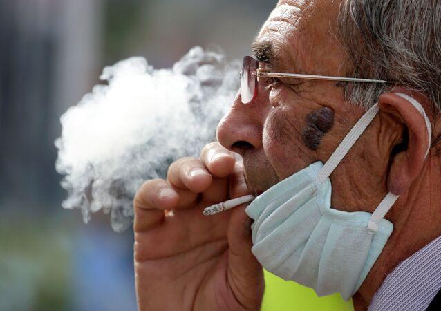 Hombre con mascarilla fumando