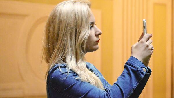 Una chica haciendo una foto con un teléfono móvil  - Sputnik Mundo