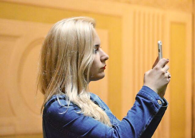 Una chica haciendo una foto con un teléfono móvil