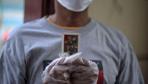 Una persona con una imagen de Jesucristo en Ecuador - Sputnik Mundo