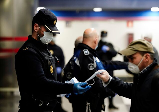 Un policía y un hombre con mascarillas en Madrid durante el brote del coronavirus