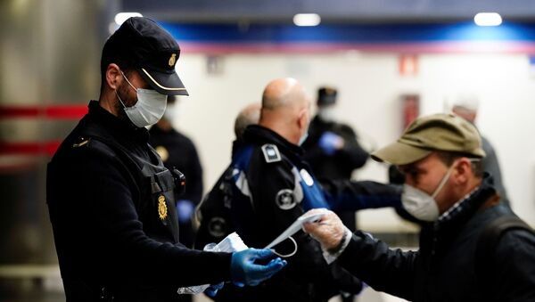 Un policía y un hombre con mascarillas en Madrid durante el brote del coronavirus - Sputnik Mundo