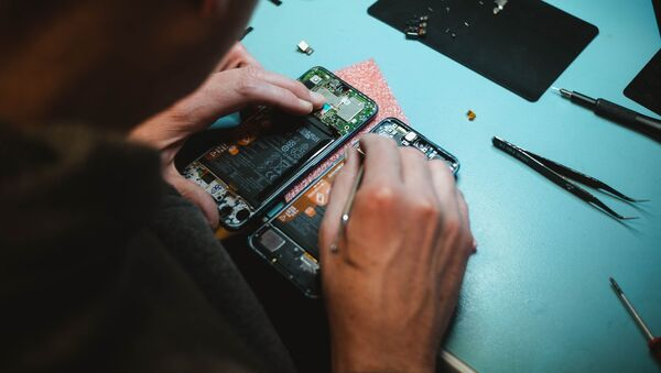 Una persona arregla un móvil - Sputnik Mundo