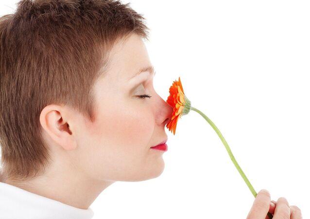 Una mujer huele una una flor