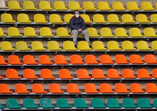 Un hombre en mascarilla en un estadio vacío