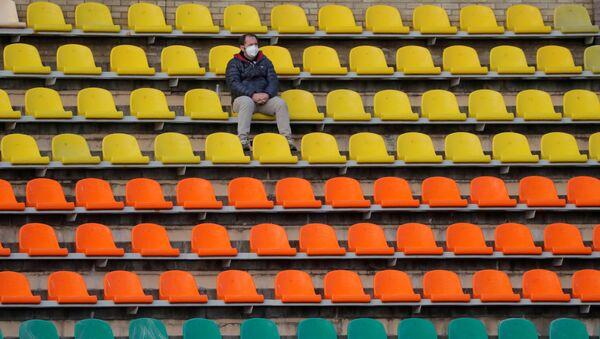 Un hombre en mascarilla en un estadio vacío - Sputnik Mundo