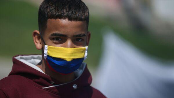 Un chico colombiano con mascarilla - Sputnik Mundo