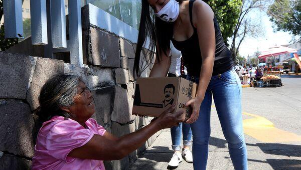 Una mujer entregando una  'Chapo despensa 701'  - Sputnik Mundo