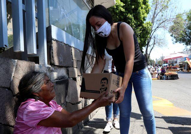 Una mujer entregando una  'Chapo despensa 701'