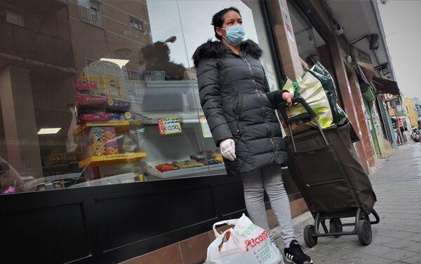 Una mujer recibe alimentos en La Brecha, una iniciativa vecinal de solidaridad de Madrid.  - Sputnik Mundo