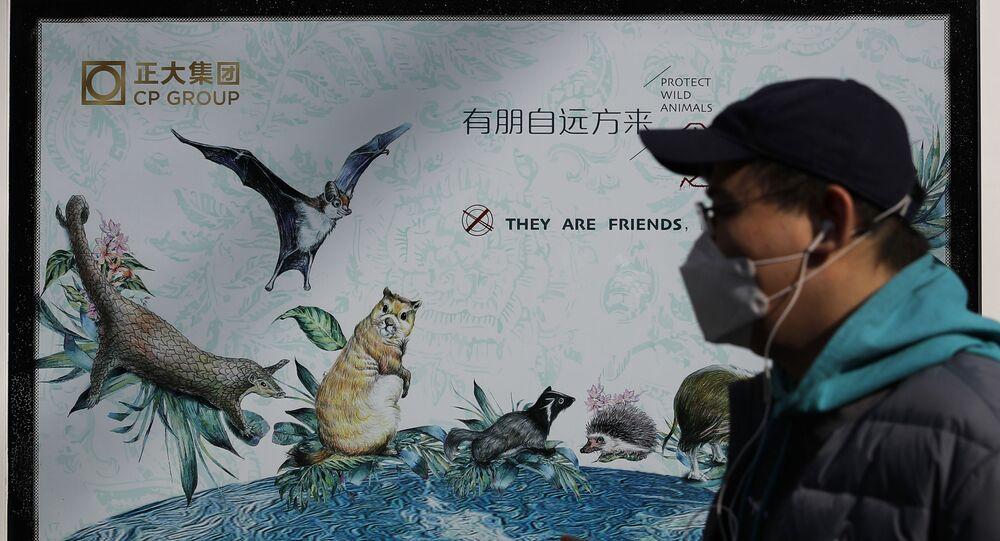 Un hombre con máscara pasa cerca de un póster publicitario que promueve la protección de los animales salvajes