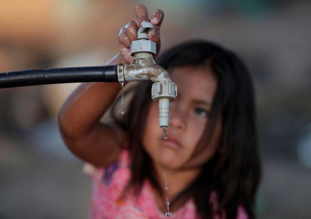 Una niña en busca de agua potable (imagen referencial)