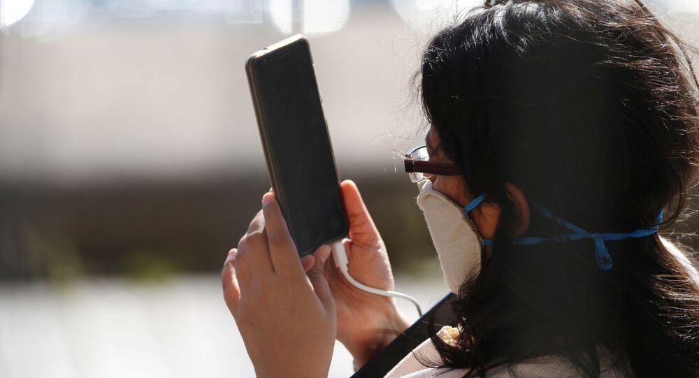Una persona con una mascarilla utiliza su móvil