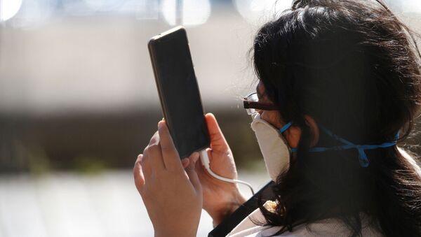 Una persona con una mascarilla utiliza su móvil - Sputnik Mundo