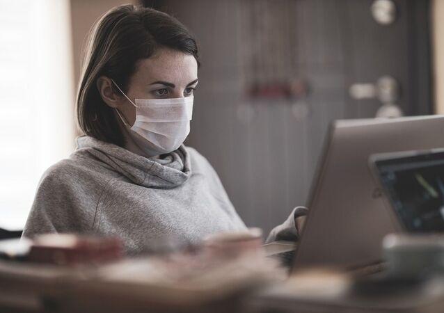 Mujer con mascarilla frente a computadora