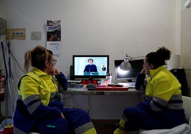 Dos empleadas observan la comparecencia de Fernando Simón
