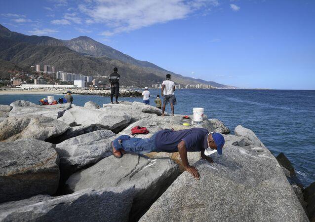 Un hombre en mascarilla entrena en la playa Los Corales en La Guaira, Venezuela