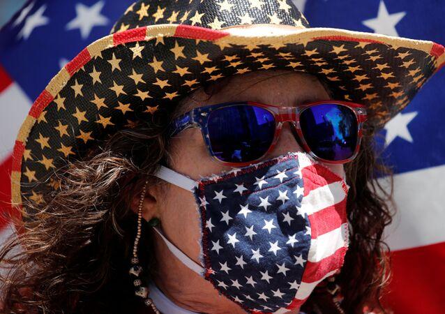 Una persona con una mascarilla con la bandera de Estados, en California