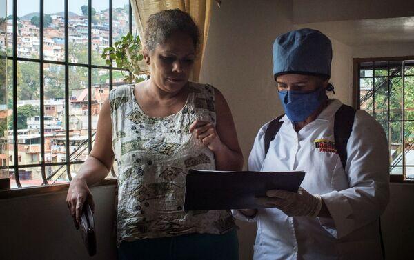 Медицинский работник во время обхода жителей для выявления случаев заболевания коронавирусом в фавелах Каракаса - Sputnik Mundo