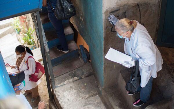 Медицинские работники во время обхода жителей для выявления случаев заболевания коронавирусом в фавелах Каракаса - Sputnik Mundo