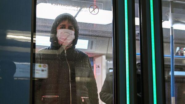 Женщина в защитной маске в вагоне поезда на станции метро Новокузнецкая в Москве - Sputnik Mundo