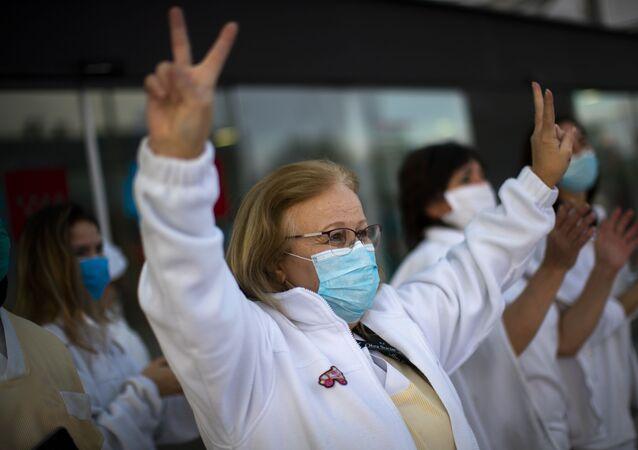 Trabajadora médica hace una señal de victoria en un gesto en apoyo al personal que está trabajando para vencer el brote del coronavirus SARS-CoV-2 en el hospital Puerta de Hierro en Majadahonda (España)
