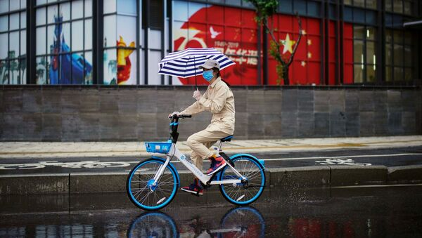 Una mujer en bicicleta con la bandera china en el fondo - Sputnik Mundo