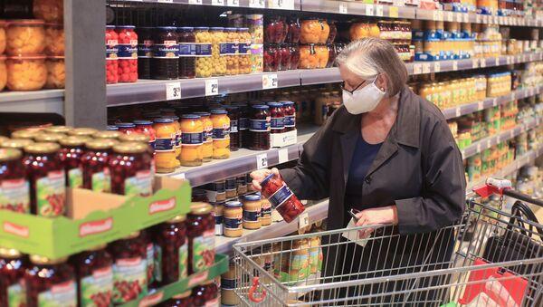 Una persona en un supermercado en plena pandemia de COVID-19 - Sputnik Mundo