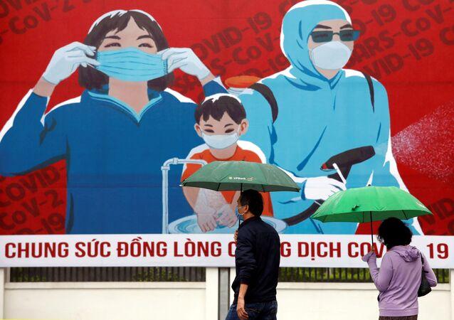 Personas con mascarillas pasan al lado de una pintura que promueve la prevención contra el COVID-19 en Hanoi, Vietnam