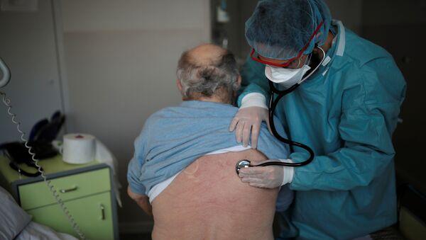 Un cardiólogo examina a un paciente en la unidad post COVID-19 de un hospital en Francia - Sputnik Mundo