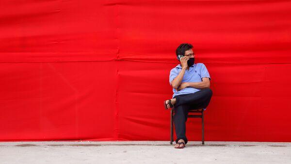 Un hombre en mascarilla hablando por teléfono - Sputnik Mundo